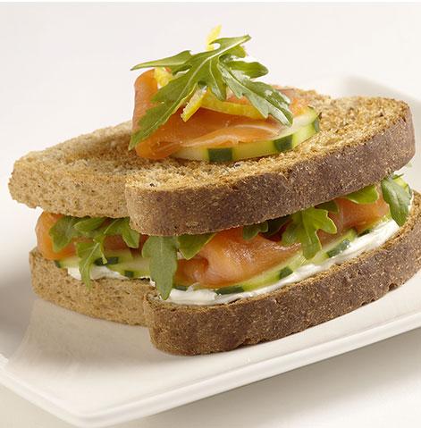 Sanduíche de salmão fumado com queijo fresco para barrar, pepino e rúcula.